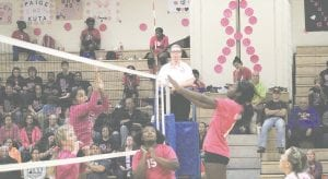 Carman-Ainsworth's Destiny Johnson, right, rises up for a shot at the net last season, while Aniya Harmon waits in the wings. Photo by Brandon Pope