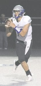 Carman-Ainsworth's Dustin Fletcher searches for an open receiver during a game last season. Photo by Kylee Richardson