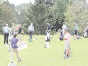 Local golfers practice on the driving range alongside professionals during Thurday's Pro-Am. Photo by Kylee Richardson