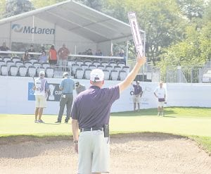A local volunteer makes sure the crowd is quiet and respectful on the 18th green last Friday. Photo by Joe Oster