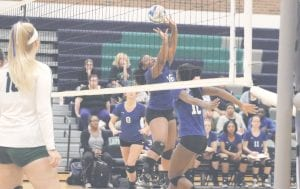 Carman-Ainsworth's Aniya Harmon (16) sets up teammate Destiny Johnson, right, for a spike against Lapeer on Sept. 11. Photo by Kylee Richardson
