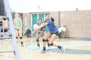 Carman-Ainsworth's Angel Eubanks, right, keeps the point alive as Diamond Lester anticipates her next move against Lapeer on Sept. 11. Photo by Kylee Richardson