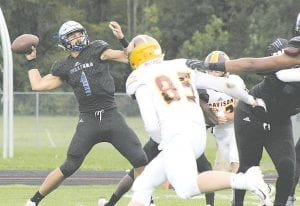 Carman-Ainsworth's Dustin Fletcher fires off a pass during a Week Three game against Davison. Photo by Brandon Pope