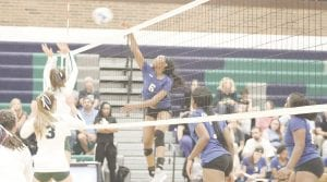 Carman-Ainsworth's Diamond Lester spikes the ball at the net against Lapeer on Sept. 11. Photo by Kylee Richardson