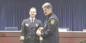 Captain Dan Kelly, right, poses with Flint Township Fire Chief Thomas Stadler as he receives his captains badge. Photo by Gary Gould