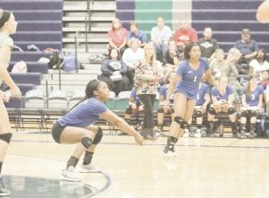 Carman-Ainsworth's Diamond Lester gets low to keep the point alive against Lapeer on Sept. 11. Photo by Kylee Richardson