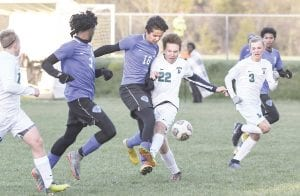 Carman-Ainsworth's Zain Shukairy battles for the ball against Lapeer during the district semifinal last Wednesday. Photo by Todd Boone