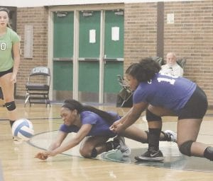 Carman-Ainsworth's Diamond Lester, left, and Aniya Harmon dive to the floor in attempt to keep the ball alive against Lapeer on Sept. 11. Photo by Kylee Richardson